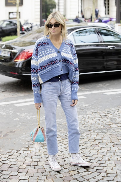 Woman wearing a sweater, jeans, and white sneakers.