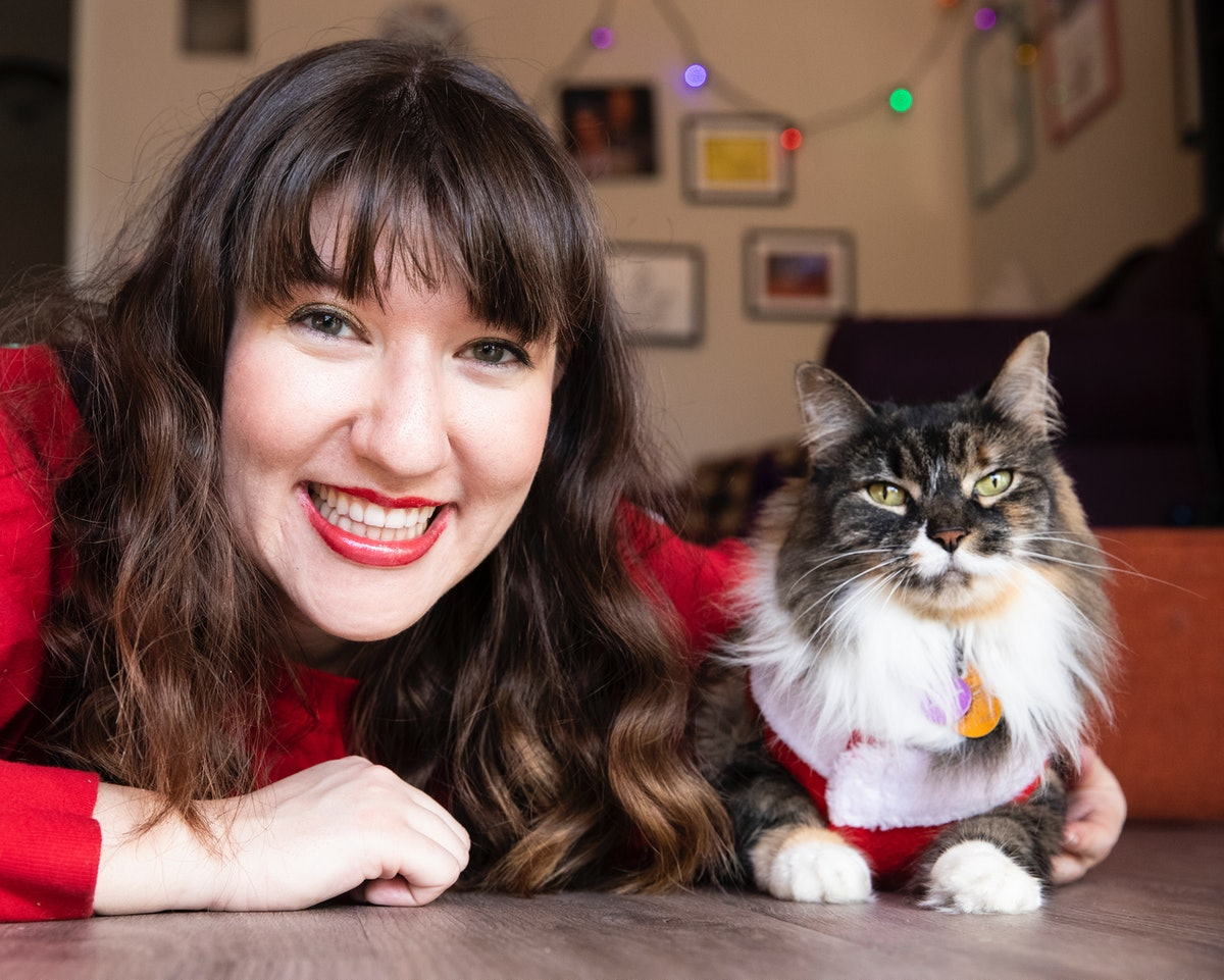 A happy brunette woman in red lipstick and a red sweater poses with her cat on the floor for a picture.