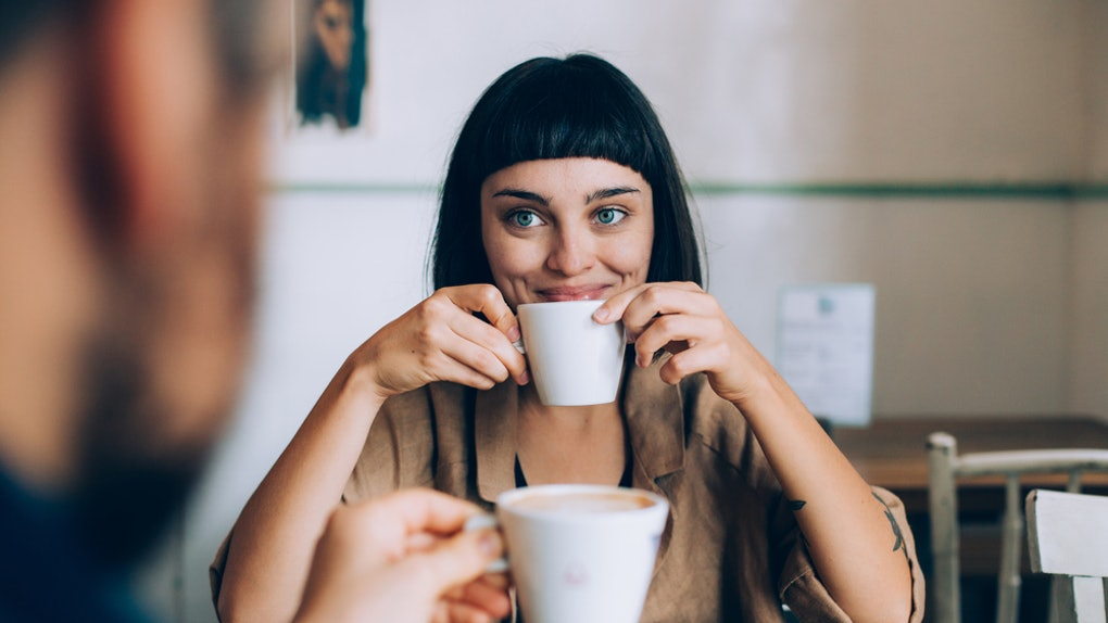 A happy woman smiles and holds up her cup of coffee while looking at her partner across the table.