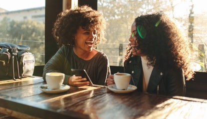 Two friends laugh at a coffee shop on a sunny day, while one of them holds a cellphone and the other holds her coffee mug.
