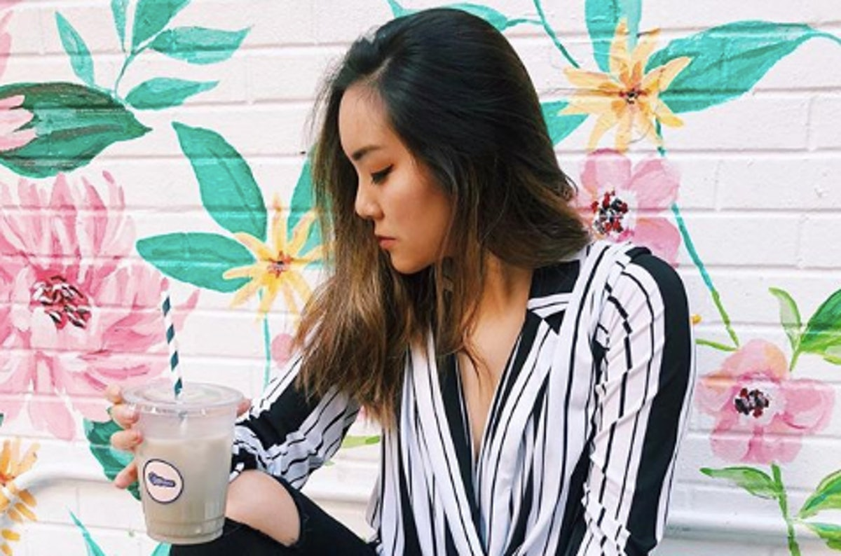 Woman holding a drink posing in front of a floral wall outside, which is one of the coolest secret Instagram spots in NYC.