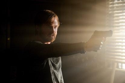 Aaron Paul as Jesse Pinkman holding a gun in the Breaking Bad finale