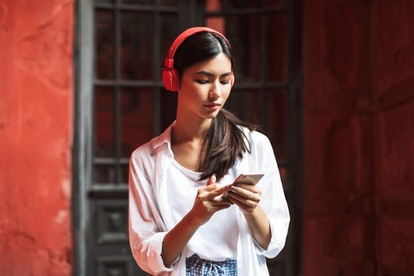 A woman in a white blouse scrolls on her phone. Set limits on your screen time in order to use your phone more mindfully