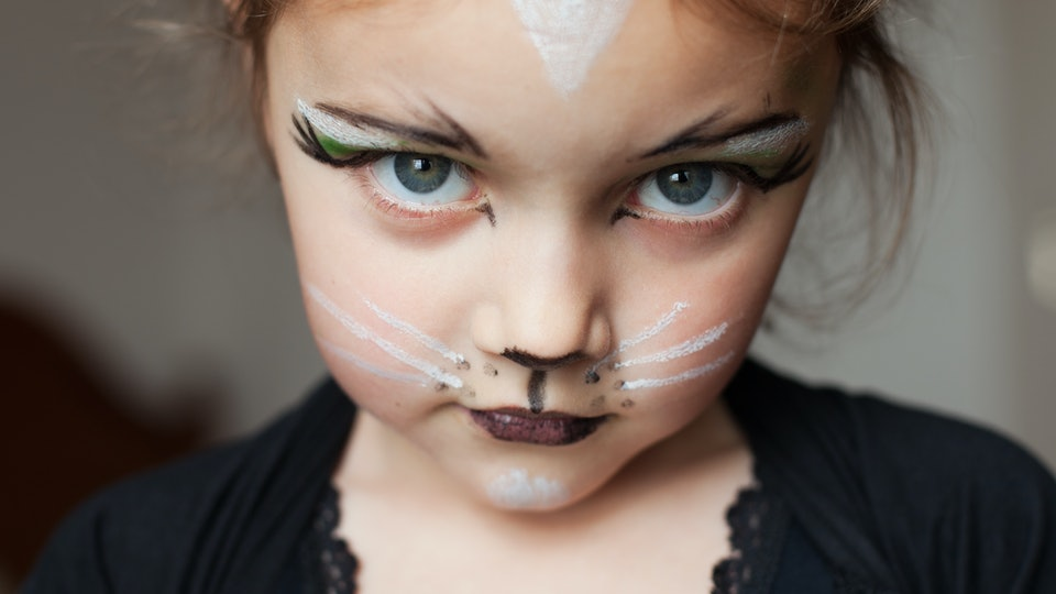 A little girl dressed as a cat with cat makeup looking at camera.