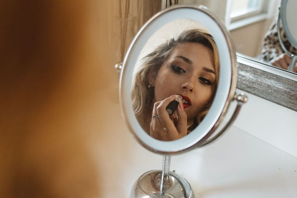 A blonde girl applies red lipstick in the mirror while she gets ready.