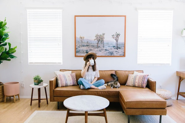 A stylish girl is sitting on a couch with a cat in a chic home like the ones on Airbnb.