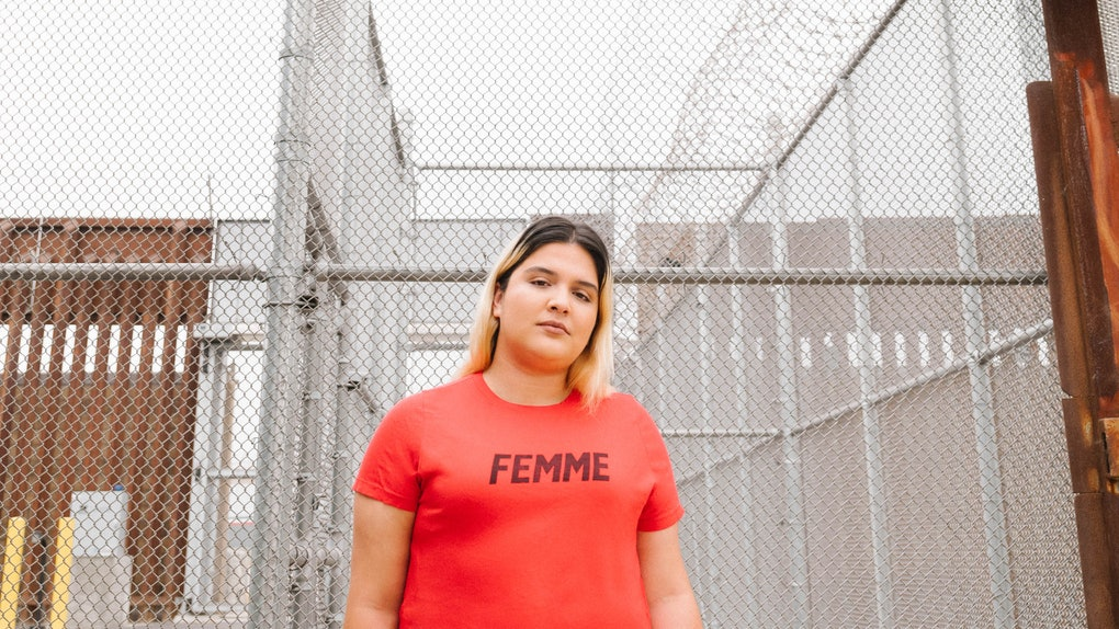 Activist Sara Mora with Girls Who Code & Team Sisterhood stands at a fence at the U.S. Mexico border