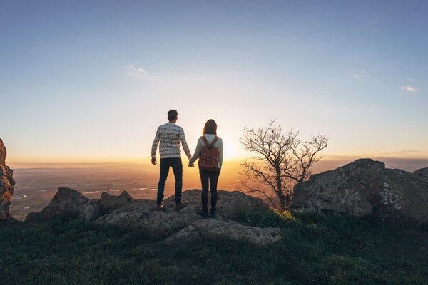 A couple holds hands at top of the mountain at sunset.
