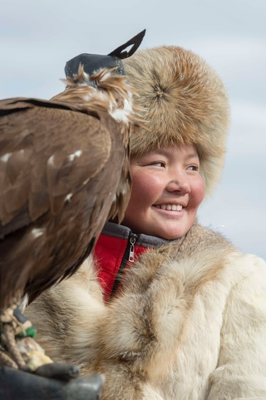 Mongolian girl proudly holds eagle on her arm.