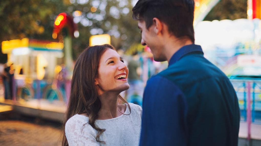 Woman smiling at her boyfriend at amusement park.
