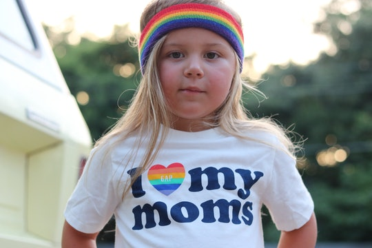 """The author's 4-year-old daughter, wearing a rainbow headband and a t-shirt that says """"I love my moms."""""""