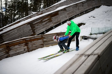 A young female ski jumper crouches as she prepares to shoot off a nordic jump with her coach.