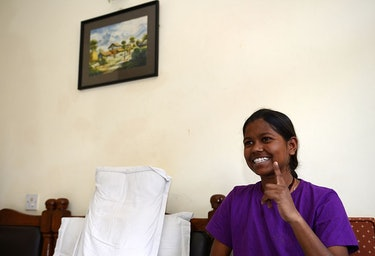 Indian girl mountaineer sits on couch smiling with finger raised.