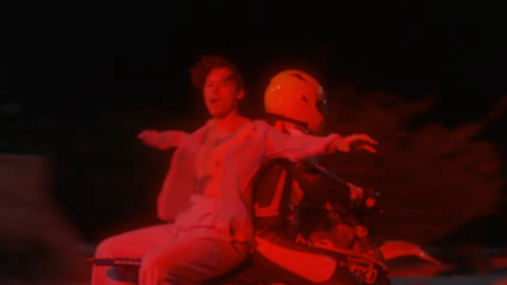 """Harry Styles rides on the back of a motorcycle in his """"Lights Up"""" music video."""