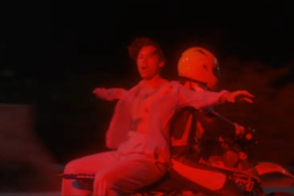 "Harry Styles rides on the back of a motorcycle in his ""Lights Up"" music video."