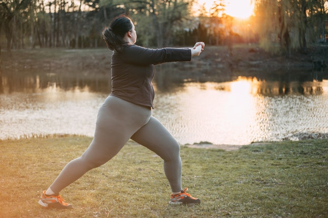 A person dressed for yoga leans into a pose near a lake at sunrise. Exercising mindfully can increase your likelihood of making your workouts a consistent habit.
