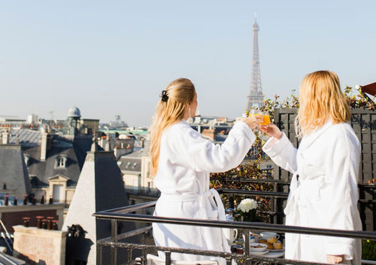 Two blonde women in bath robes are toasting and having breakfast on their balcony at their Airbnb in Paris.