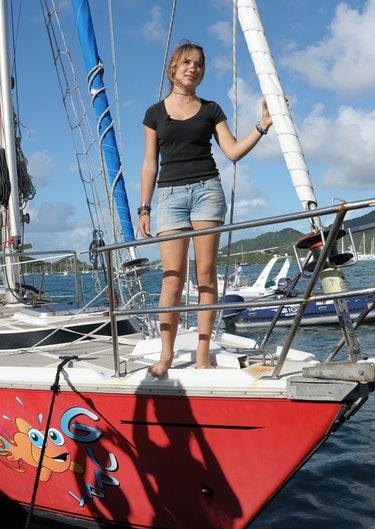 Girl stands on bow of yacht as it enters a harbor.