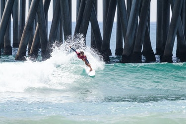 A teenaged surfer balances on top of a wave by a pier.