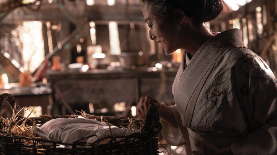 Kiki Sukezane as Yuko standing over a baby in a basket in The Terror: Infamy