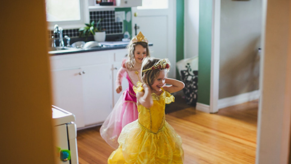 Two young girls in a yellow and pink princess dress run through a doorway.