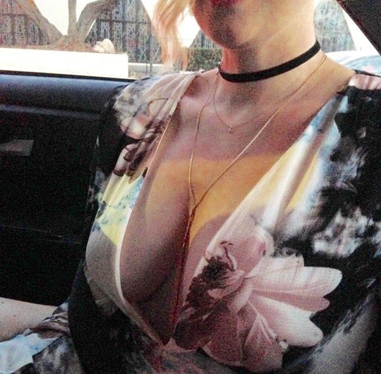 A woman's chest is visible, dressed in a floral dress.