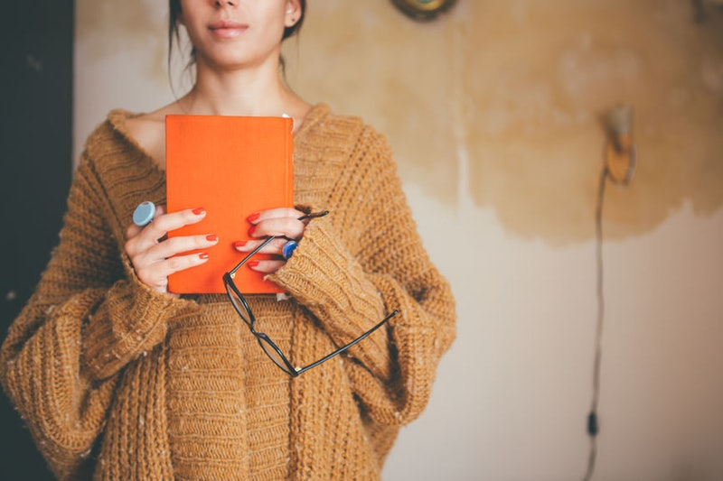 A woman in a sweater clutches an orange hardcover book, in this list of horror novels to read, based on your zodiac sign.