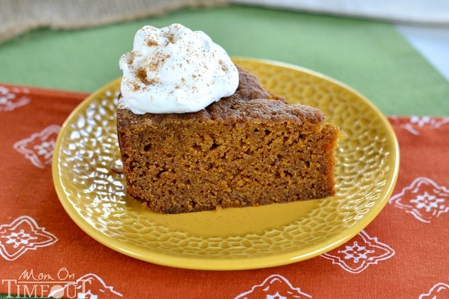 slow cooker pumpkin pie cake with whipped cream sitting on yellow plate
