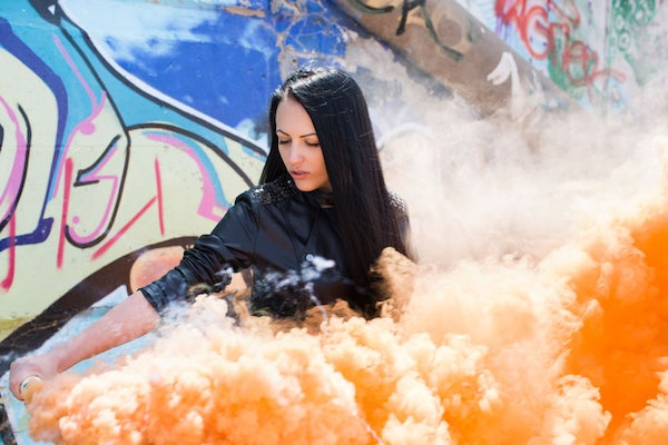 A woman stands next to a wall covered in graffiti in the city with orange smoke around her.