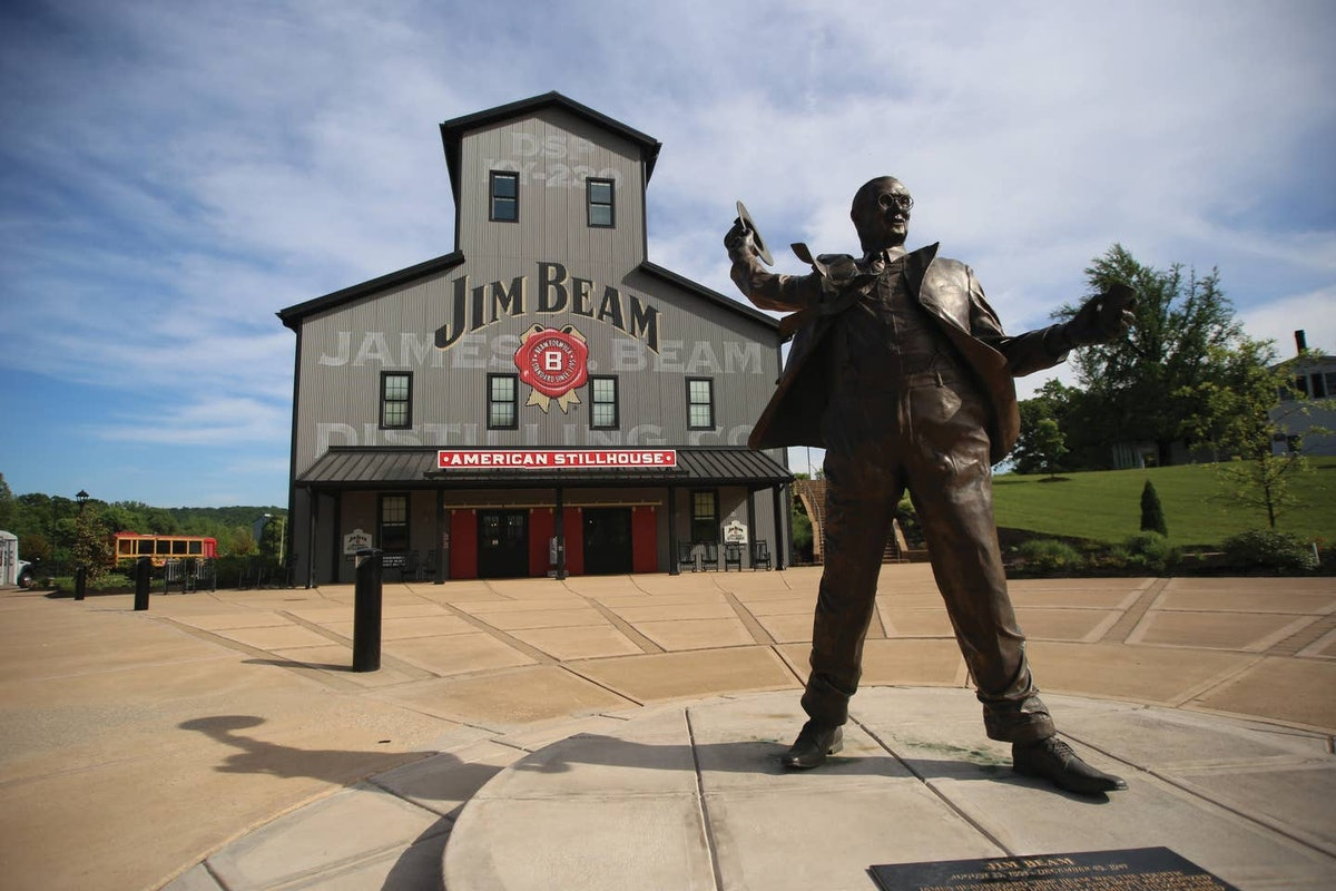 An exterior view of the Jim Beam American Stillhouse with a statue of Jim Beam in the front.