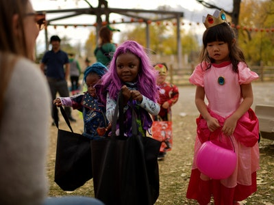 a girl in a purple wig and a girl dressed as a pink princess hold out pumpkin baskets for candy on Halloween night.