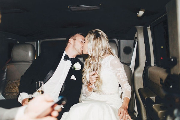 A bride and groom kissing on their wedding day in a limo with champagne is the perfect picture to post on Instagram for your parents' anniversary.