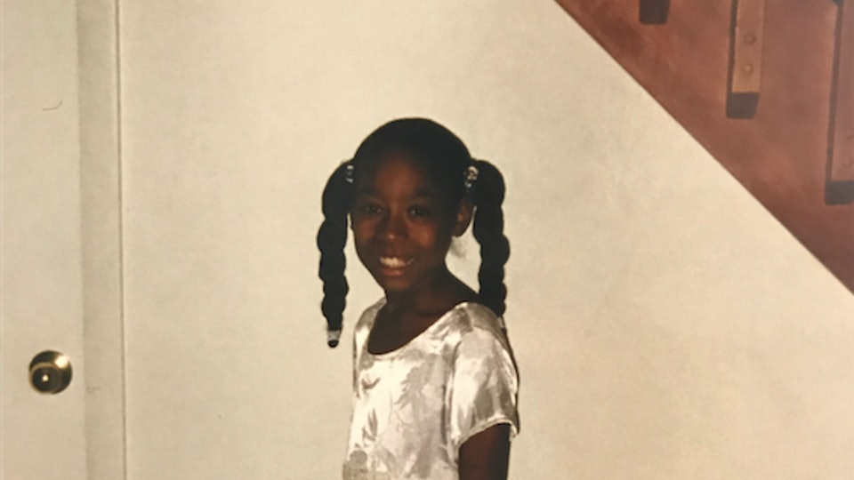 The author as a young child, standing in a white dress smiling at the camera.