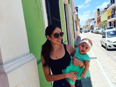 A woman stands on street in Mexico against green wall holding a baby.