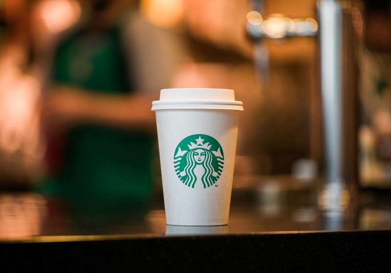 A white, paper Starbucks hot cup with the green siren logo on it sitting on a tabletop.