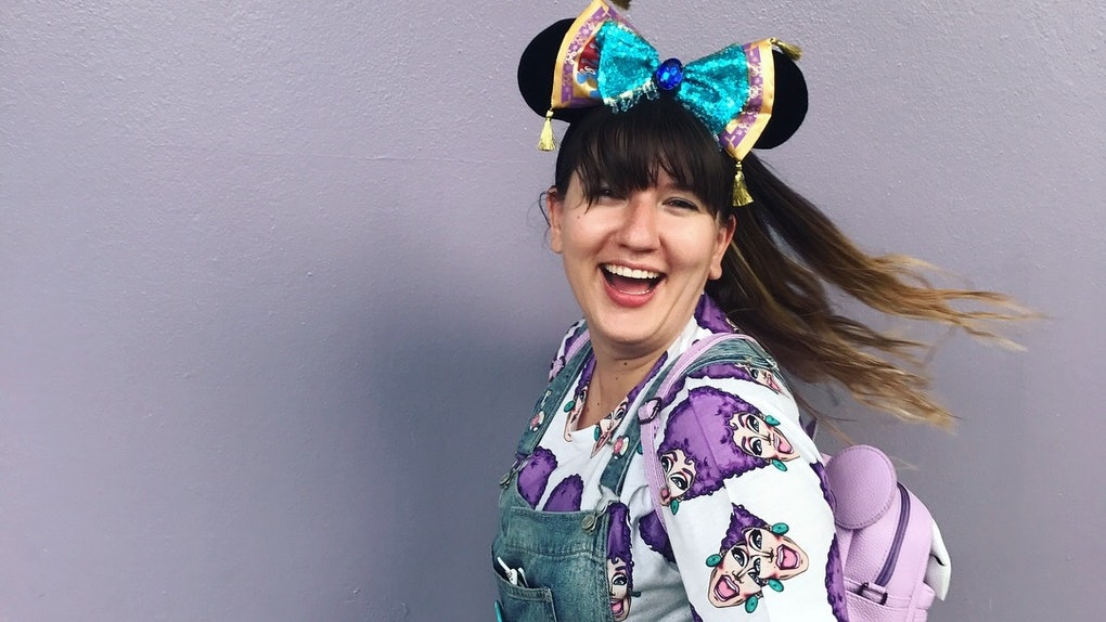 A woman smiles in front of a purple wall, wearing overalls, Minnie ears, and a purple backpack at Disney World.