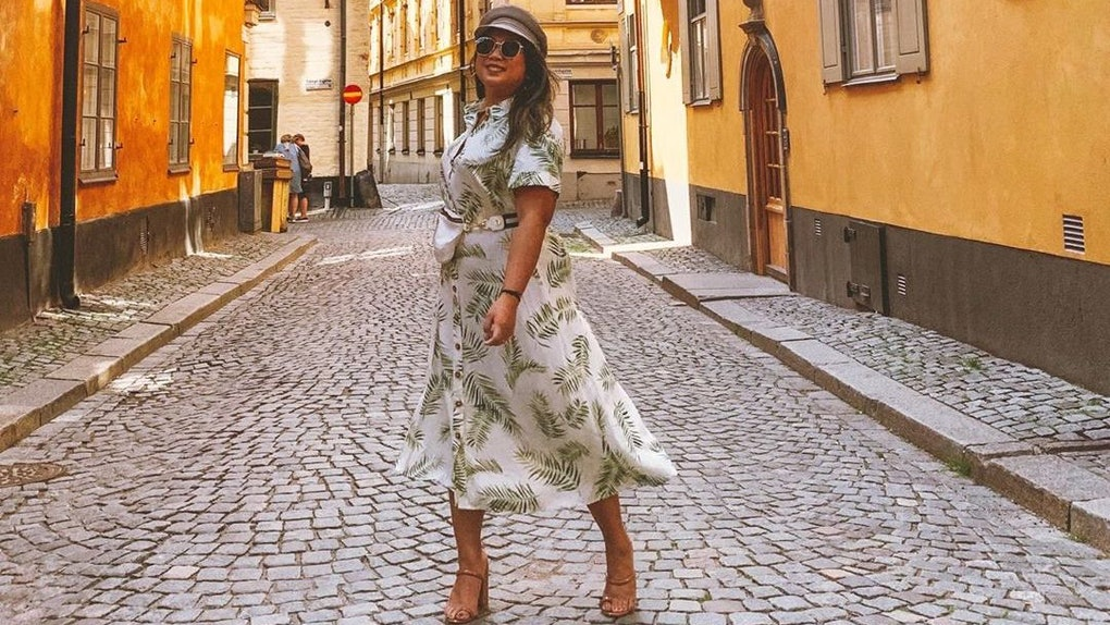 A girl smiles in a tropical-printed dress, hat, and pair of nude heels that are just one of the most stylish walking shoes for travel.