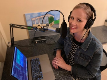 Woman sits with headphones on recording a podcast.