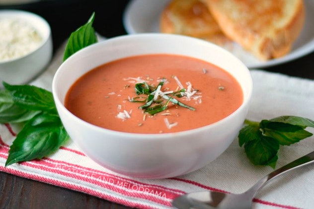 Tomato soup in a white bowl with grilled cheese sandwich in the background.