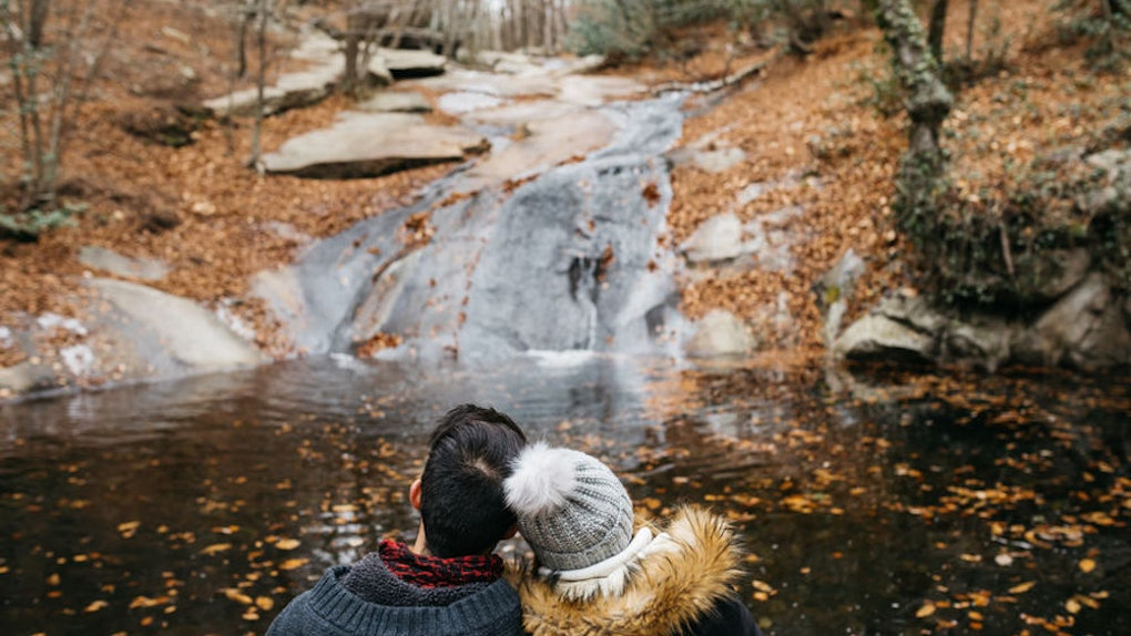A couple cuddles and sits in front of a small waterfall in a forest with lots of fall foliage for leaf peeping.