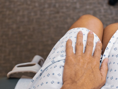 A patient in a medical gown awaits the results of an STI test