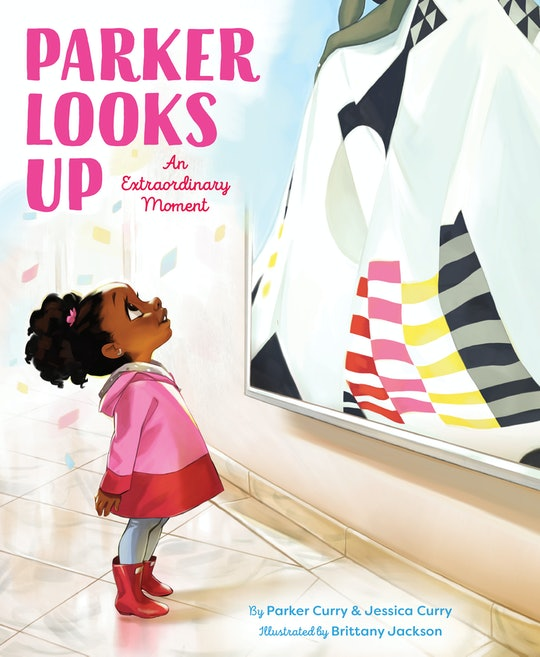 """A little girl looks up at a portrait of Michelle Obama on the cover of """"Parker Looks Up"""""""