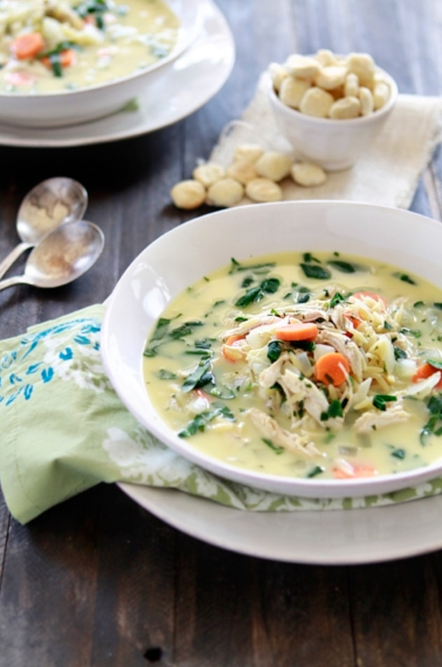 Instant pot lemon chicken spinach and orzo soup in a white bowl with oyster crackers in the backgrou...