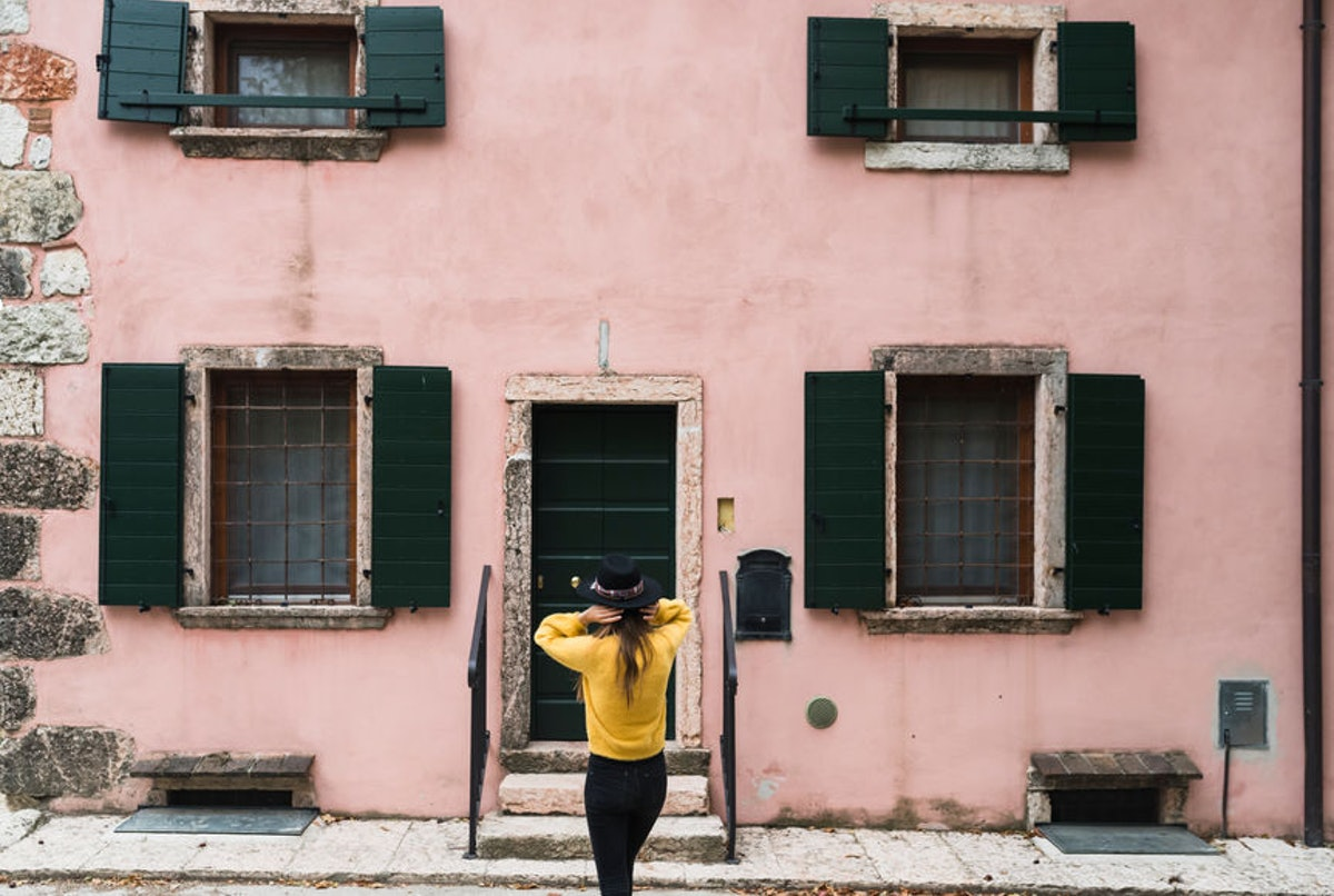 A stylish girl in a yellow sweater and black felt hat stands in front of a pink, rustic building.