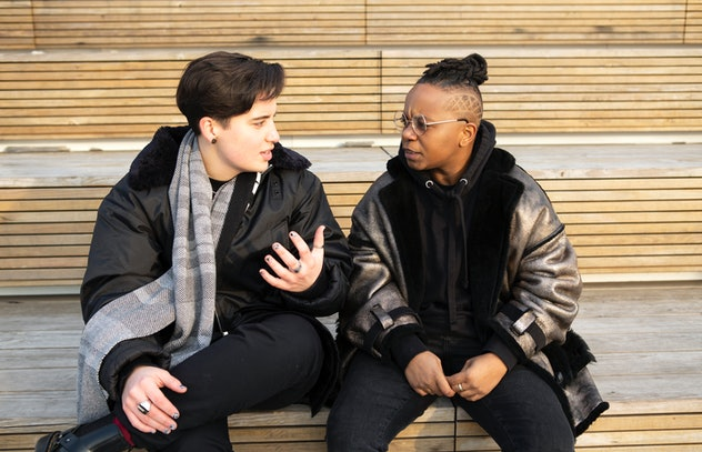Two transmasculine people sitting together and having a serious conversation.