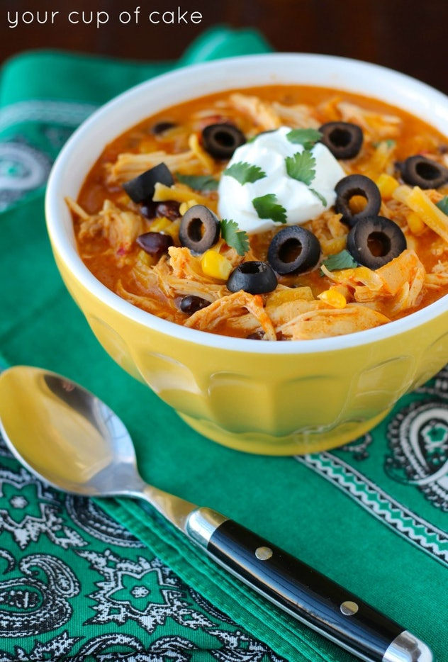slow cooker chicken enchilada soup in yellow bowl on green placemat