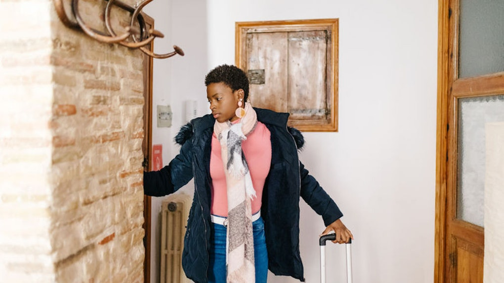 A woman wearing a jacket, sweater, scarf, and jeans stands near the door of a cozy apartment with a red suitcase.