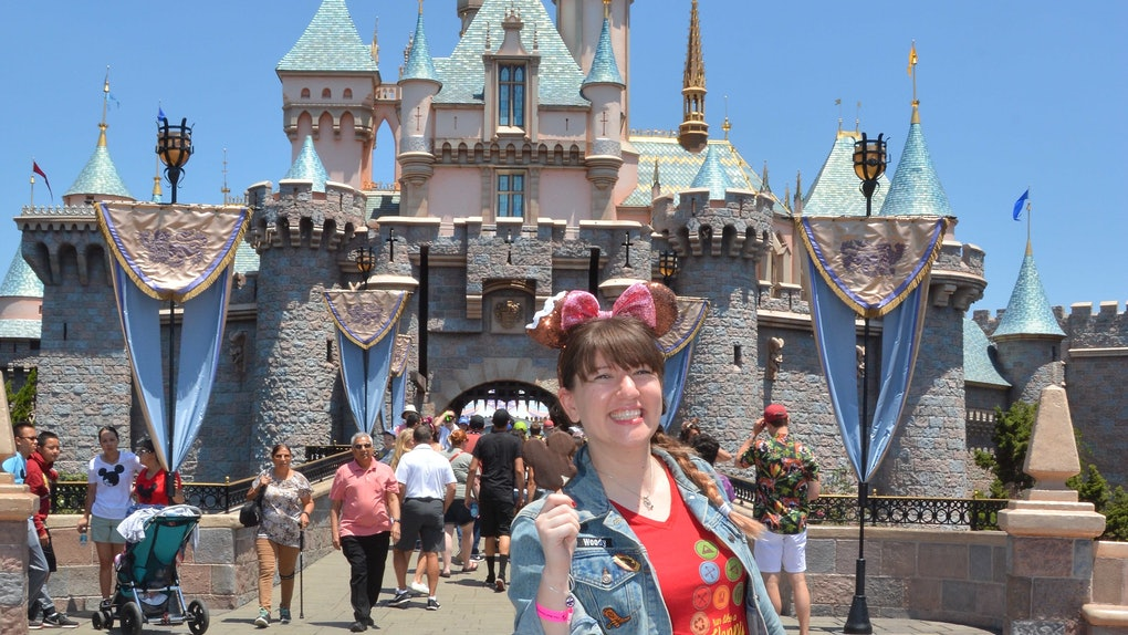 A woman holding a Mickey ice cream in front of the castle would need Mickey-shaped food captions for Instagram.
