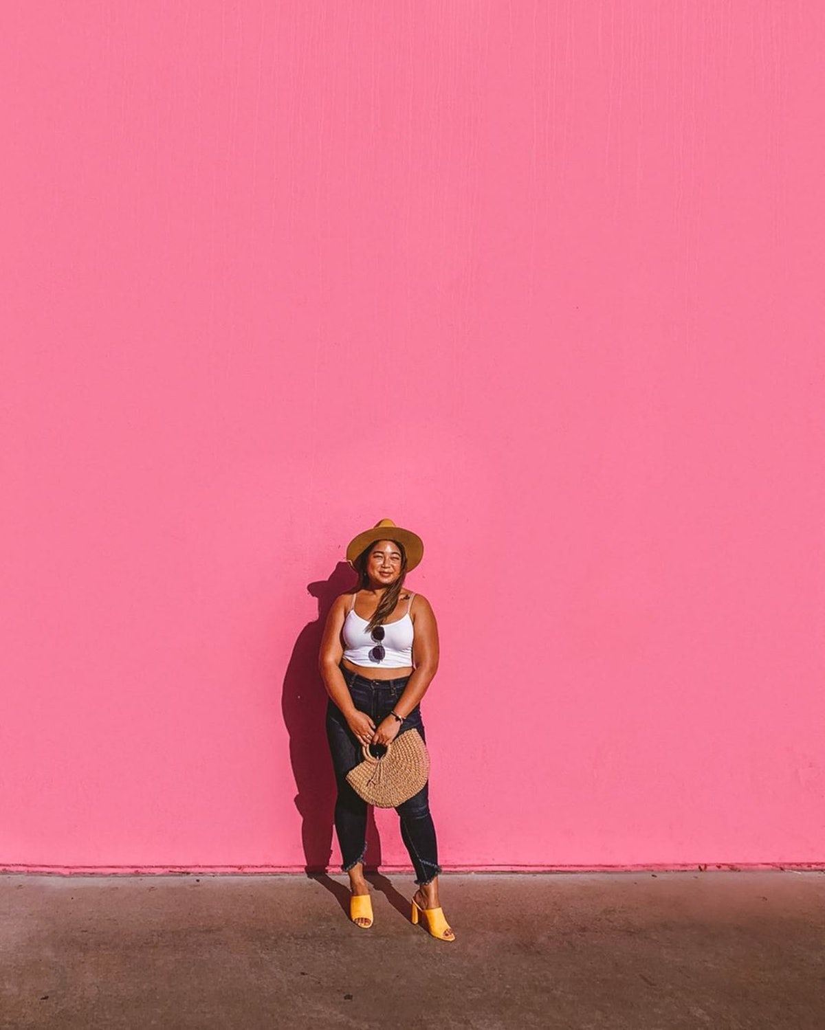 A woman in a white tank top, blue jeans, and yellow heels standing in front of the Paul Smith pink wall. She's thinking about how moving to Los Angeles from NYC is a great idea.