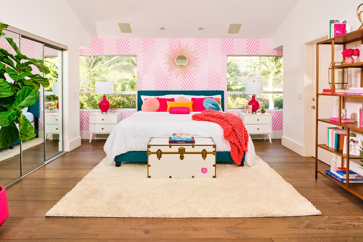 The master bedroom in Barbie's Malibu Dreamhouse is decorate with brightly-colored pillows, a fuzzy rug, and a white trunk with travel books on top.